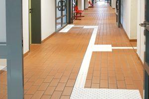 Taktile Besucherführung im Flur mit weißen Bodenindikatoren aus Platten