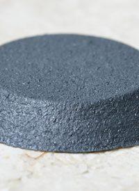 Schwarze Noppe auf Steinboden