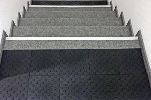 Taktile Noppenplatte in schwarz als Aufmerksamkeitsfeld vor einer Treppe